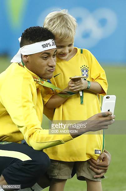 Brazil's forward Neymar takes a selfie with his son after the Rio 2016 Olympic Games men's football gold medal match between Brazil and Germany at...