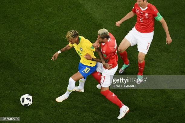 TOPSHOT Brazil's forward Neymar vies with Switzerland's midfielder Valon Behrami during the Russia 2018 World Cup Group E football match between...