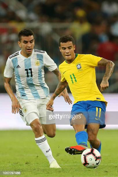 Brazil's forward Philippe Coutinho passes the ball next to Argentina's forward Angel Correa during the friendly football match Brazil vs Argentina at...