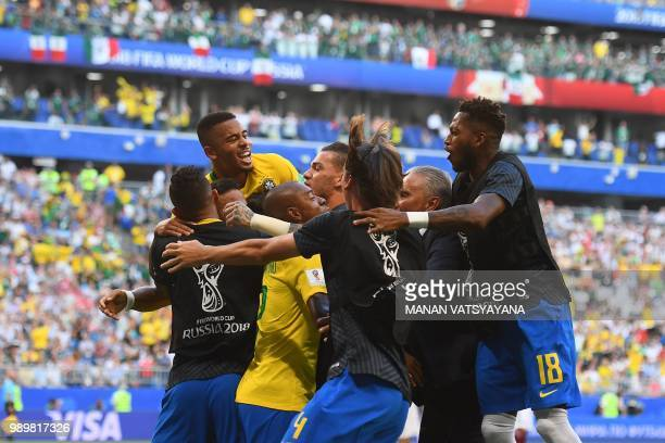 Brazil's forward Roberto Firmino celebrates with teammates after scoring a goal during the Russia 2018 World Cup round of 16 football match between...