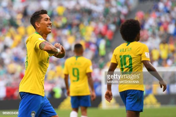 Brazil's forward Roberto Firmino gestures as he celebrates after scoring a goal during the Russia 2018 World Cup round of 16 football match between...