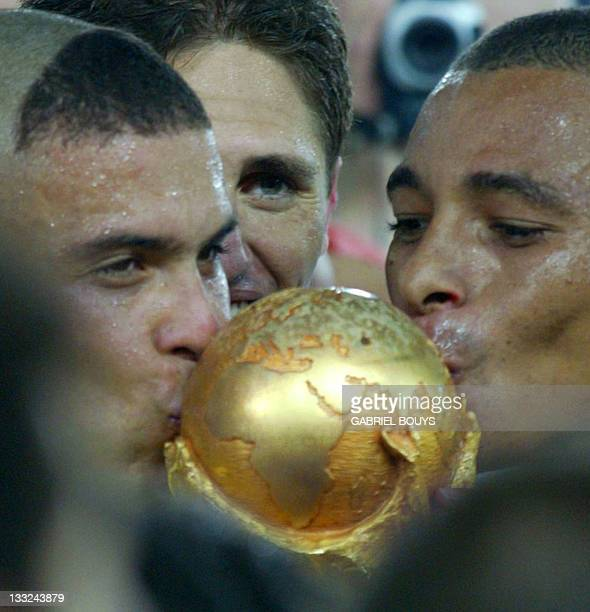 Brazil's forward Ronaldo and Brazil's midfielder Gilberto Silva kiss the trophy and are joined by teammate Edmilson at the trophy ceremony after the...