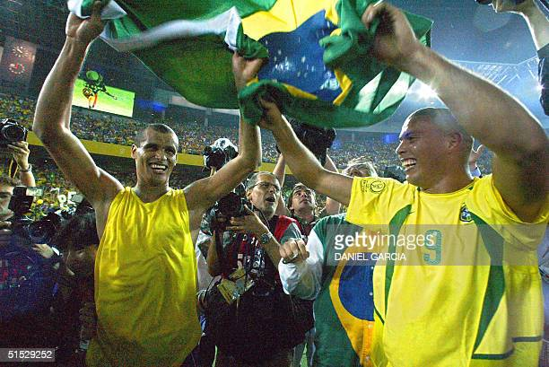 Brazil's forward Ronaldo and midfielder Rivaldo are all smiles as they wave the national colors celebrating their 20 victory against Germany in match...