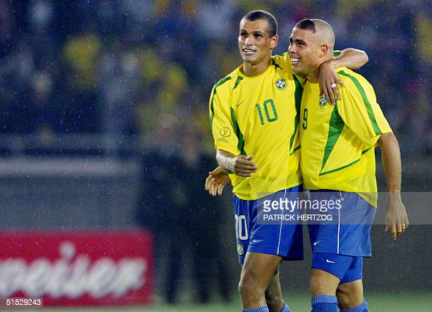 Brazil's forward Ronaldo and teammate midfielder Rivaldo hug in the rain after Ronaldo scored the second goal against Germany in match 64 of the 2002...