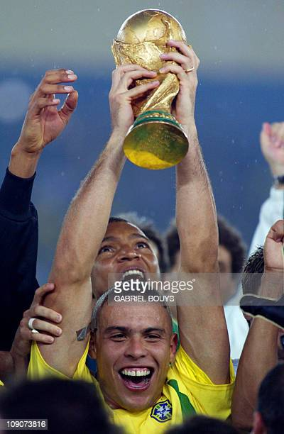 Brazil's forward Ronaldo hoists the World Cup trophy during the award ceremony at the International Stadium Yokohama Japan 30 June 2002 following...