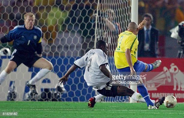 Brazil's forward Ronaldo scores the second goal against Germany's team captain and goalkeeper Oliver Kahn despite the defense of forward Gerald...