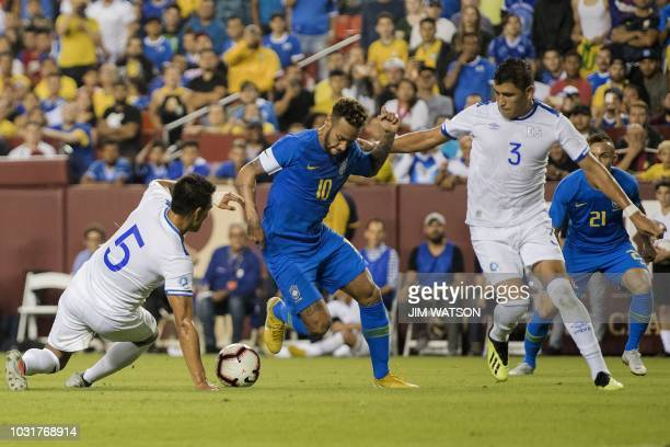 Brazil's foward Neymar vies for the ball with El Salvador's defenders Alexander Mendoza and Roberto Dominguez during the international friendly match...