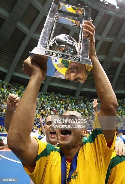 Brazil's futsal team player Cico celebrates with the trophy after defeating Spain to win the championship on October 19 2008 in their FIFA Futsal...