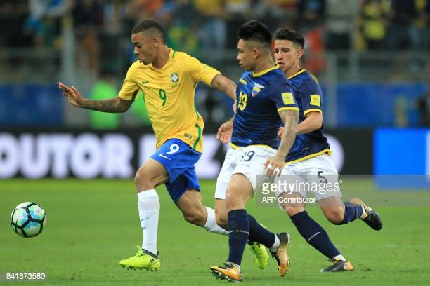 Brazil's Gabriel Jesus is marked by Ecuador's Cristian Ramirez and Fernando Gaibor during their 2018 World Cup qualifier football match in Porto...