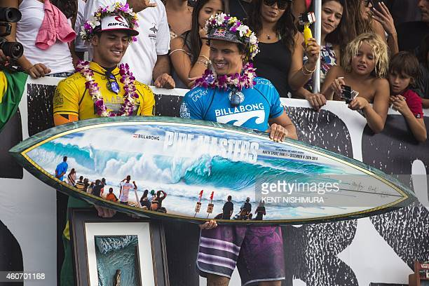 Brazil's Gabriel Medina and Australia's Julian Wilson stand on stage during the awards ceremony on the final day of the Billabong Pipeline Masters...