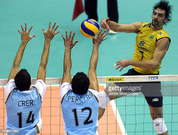 Brazil's Gilberto Godoy Filho spikes the ball agaist Argentina's Pablo Crer and Federico Pereira during their Volleyball World League semifinal game...