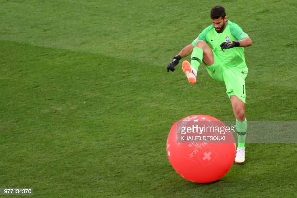 Brazil's goalkeeper Alisson bursts a balloon during the Russia 2018 World Cup Group E football match between Brazil and Switzerland at the Rostov...