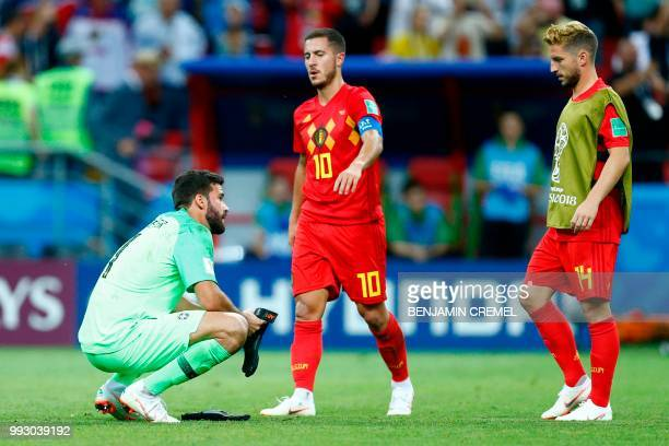 Brazil's goalkeeper Alisson crouches on the field as Belgium's forward Eden Hazard and Belgium's forward Dries Mertens walk past at the end of the...