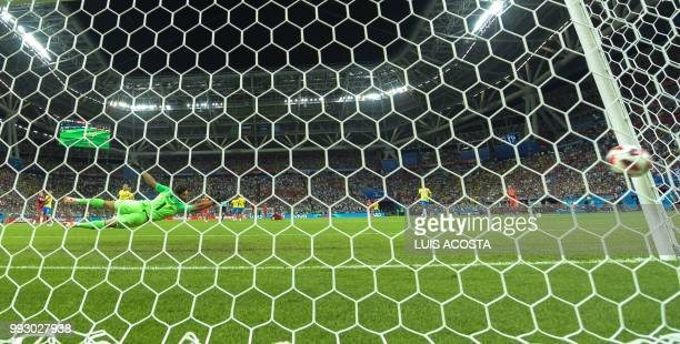 Brazil's goalkeeper Alisson dives and fails to stop a goal by Belgium's midfielder Kevin De Bruyne during the Russia 2018 World Cup quarterfinal...