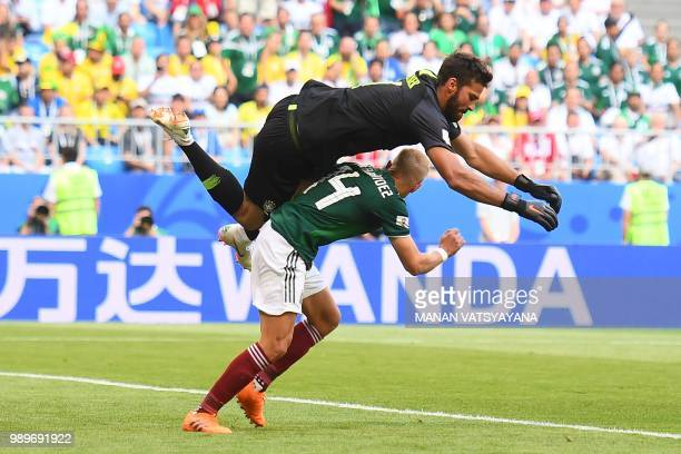 Brazil's goalkeeper Alisson jumps over Mexico's forward Javier Hernandez as they vie for the ball during the Russia 2018 World Cup round of 16...