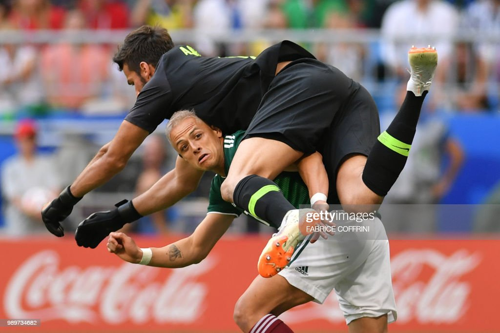 TOPSHOT - Brazil's goalkeeper Alisson jumps over Mexico's forward Javier Hernandez as they vie for the ball during the Russia 2018 World Cup round of 16 football match between Brazil and Mexico at the Samara Arena in Samara on July 2, 2018. (Photo by Fabrice COFFRINI / AFP) / RESTRICTED