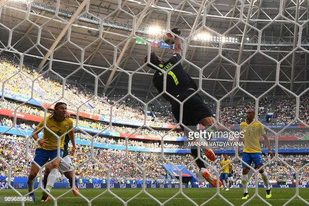 Brazil's goalkeeper Alisson jumps to catch the ball during the Russia 2018 World Cup round of 16 football match between Brazil and Mexico at the...