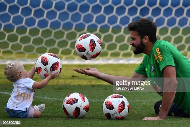 TOPSHOT Brazil's goalkeeper Alisson players with his daughter Helena during a training session at the Yug Sport Stadium in Sochi on July 3 ahead of...