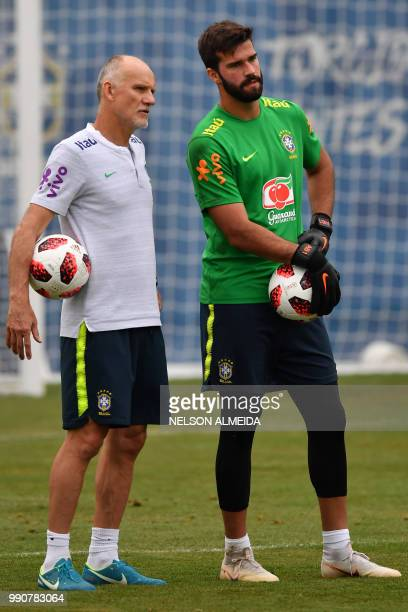 Brazil's goalkeeper coach and former World Cup 1994 champion Claudio Taffarel speaks with Brazil's goalkeeper Alisson during training session at the...