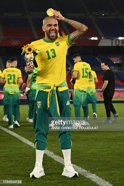 Brazil's gold medallist Dani Alves celebrates after receiving his medal on the podium during the medal ceremony of the Tokyo 2020 Olympic Games men's...