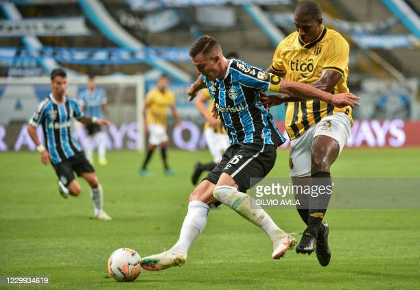 Brazil's Gremio Argentine Diego Churin is challenged by Paraguay's Guarani Colombian Jhohan Romana during their closed-door Copa Libertadores round...