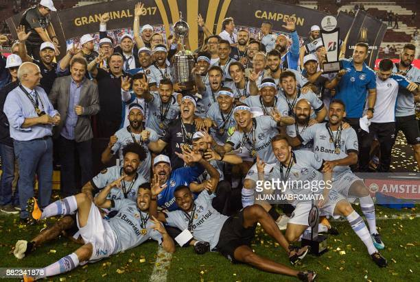 Brazil's Gremio celebrate with the trophy after winning the Copa Libertadores 2017 final football match against Argentina's Lanus at Lanus stadium in...