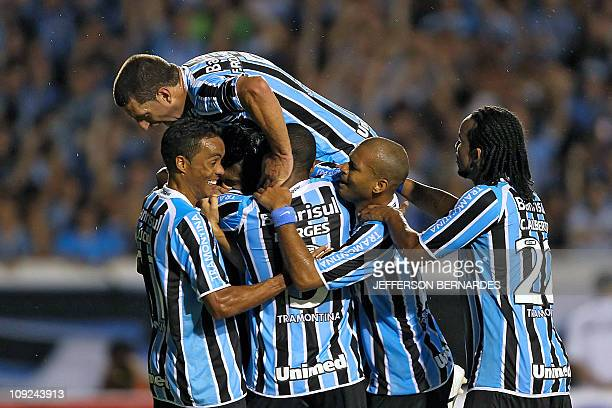 Brazil's Gremio footballer Gilson is hugged by teammates after scoring against Oriente Petrolero of Bolivia during a Libertadores Cup match at the...