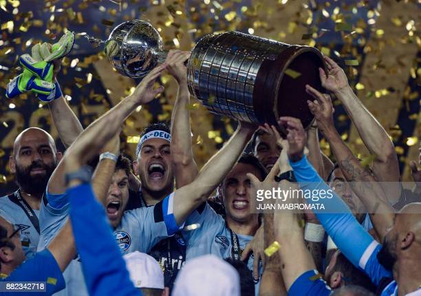 Brazil's Gremio footballers celebrate with the trophy after winning the Copa Libertadores 2017 final football match against Argentina's Lanus at...