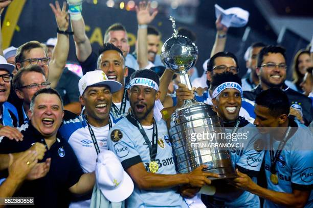 Brazil's Gremio footballers celebrate with the trophy after winning the Copa Libertadores 2017 final football match 21 against Argentina's Lanus at...