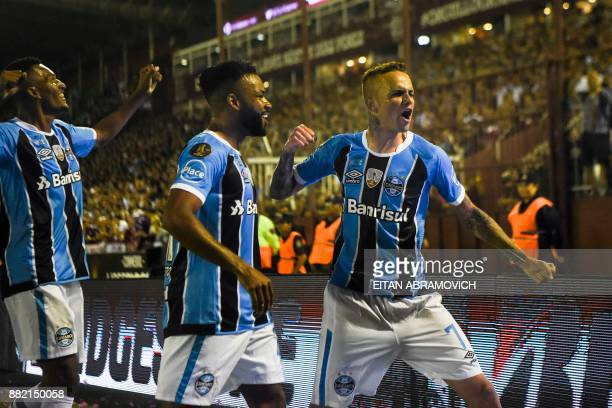 Brazil's Gremio forward Luan celebrates with teammate forward Fernandinho after scoring a goal against Argentina's Lanus during the Copa Libertadores...