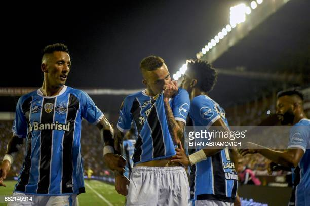 Brazil's Gremio forward Luan celebrates with teammate forward Lucas Barrios after scoring a goal against Argentina's Lanus during the Copa...