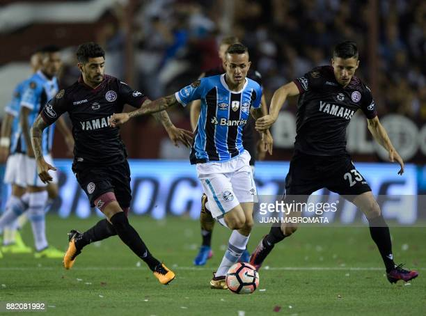 Brazil's Gremio forward Luan vies for the ball with Argentina's Lanus defender Rolando Guerreno and midfielder Roman Martinez during their Copa...