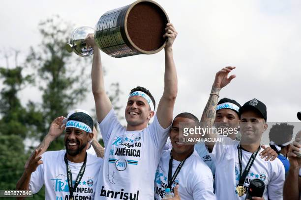 TOPSHOT Brazils Gremio goalkeeper Marcelo Grohe raises the Copa Libertadores 2017 trophy next to his teammates as he celebrates their victory in...