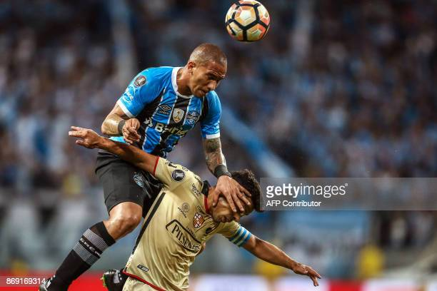 TOPSHOT Brazil's Gremio Jailson jumps for the ball over Matias Oyola of Ecuador's Barcelona during their 2017 Libertadores Cup football match held at...
