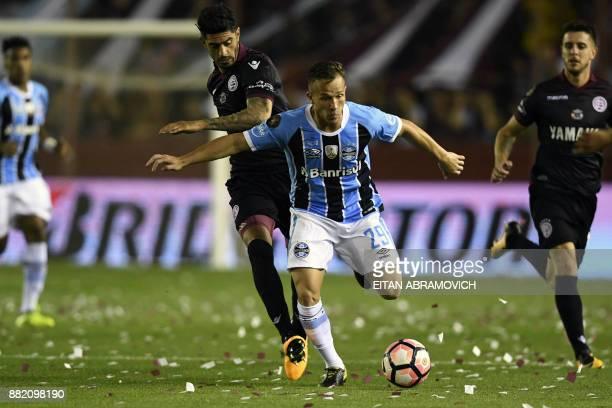 Brazil's Gremio midfielder Arthur vies for the ball with Argentina's Lanus midfielder Roman Martinez during their Copa Libertadores 2017 final...