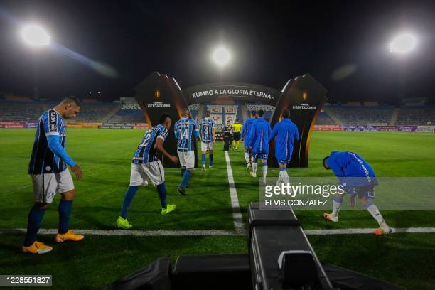 Brazil's Gremio players and Chile's Universidad Catolica players enter the field for their closeddoor Copa Libertadores group phase football match at...