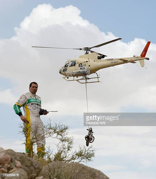 Brazil's Guilherme Spinelli observes his Mitsubishi stuck in a river below as a helicopter passes with an unidentified bike during Stage 8 of the...