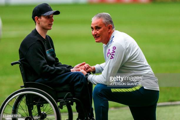 Brazil's head coach Tite speaks with a fan before a training session at Beira-Rio stadium in Porto Alegre, Brazil on June 8 ahead of the Copa America...