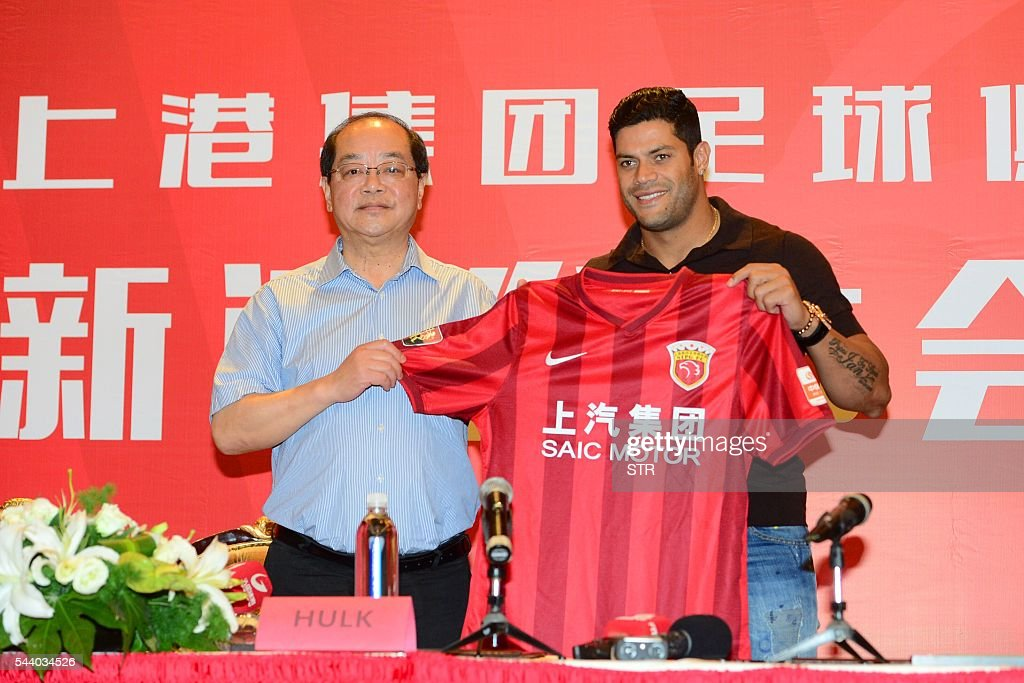Brazil's Hulk (R) poses with his new jersey during a press conference for joining Shanghai SIPG Football Club in Shanghai on July 1, 2016. Zenit St Petersburg's Brazilian international Hulk arrived in Shanghai on June 29 to sign for Sven-Goran Eriksson's Shanghai SIPG team, as the cash-flush Chinese Super League embarks on a new round of transfer spending. / AFP / STR / China OUT