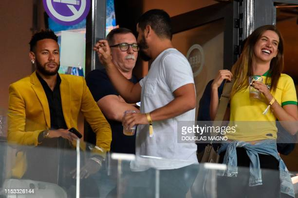 Brazil's injured football star Neymar is seen at the VIP area before the Copa America football tournament semifinal match between Brazil and...