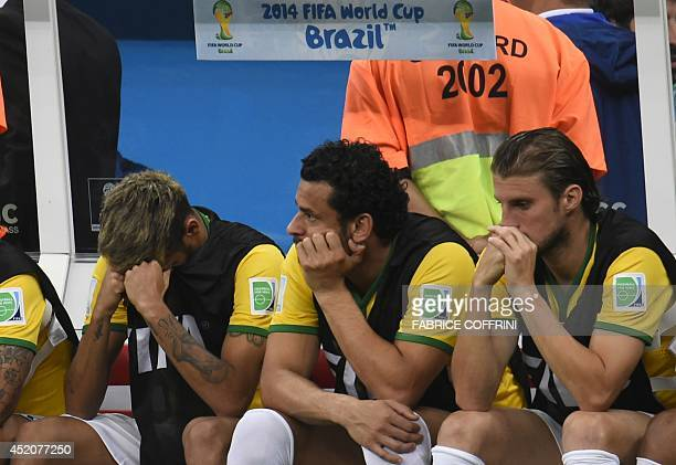 Brazil's injured forward Neymar Brazil's forward Fred and Brazil's defender Henrique react on the bench at the end of the third place playoff...
