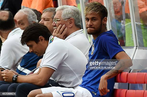 Brazil's injured forward Neymar sits on the bench before the third place playoff football match between Brazil and Netherlands during the 2014 FIFA...