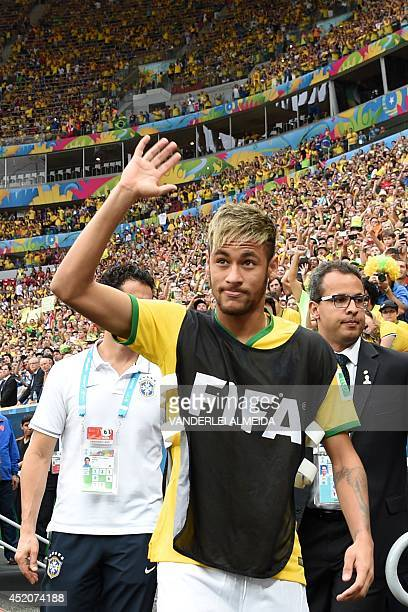 Brazil's injured forward Neymar waves at supporters as he walks towards the bench during the third place playoff football match between Brazil and...