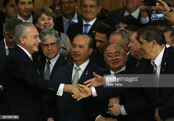 Brazil's interim President Michel Temer is greeted by supporters at a signing ceremony for new government ministers at the Planalto presidential...