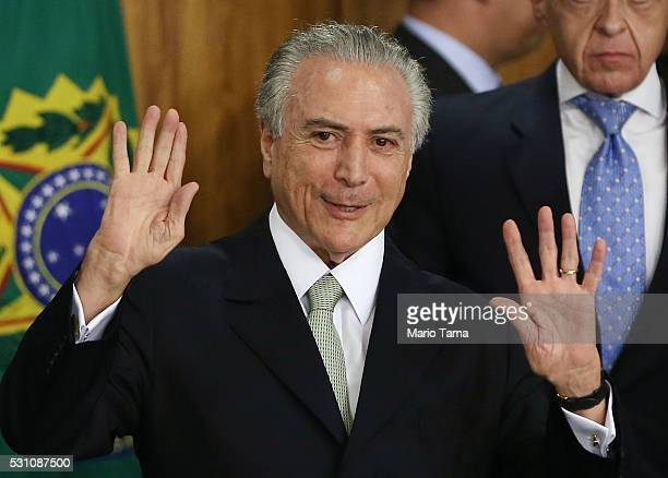 Brazil's interim President Michel Temer waves at a signing ceremony for new government ministers at the Planalto presidential palace after the Senate...