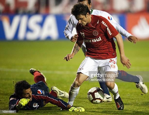 Brazil's Internacional footballer Rafael Sobis struggles for the ball with goalkeeper Luis Ernesto of Mexico's Chivas during their Libertadores Cup...