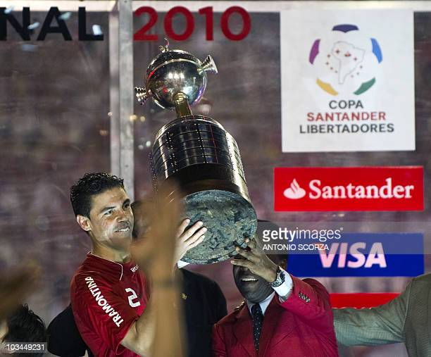 Brazil's Internacional player Bolivar holds up the Libertadores Cup with Brazilian football legend Pele on August 18 2010 at Beira Rio stadium in...