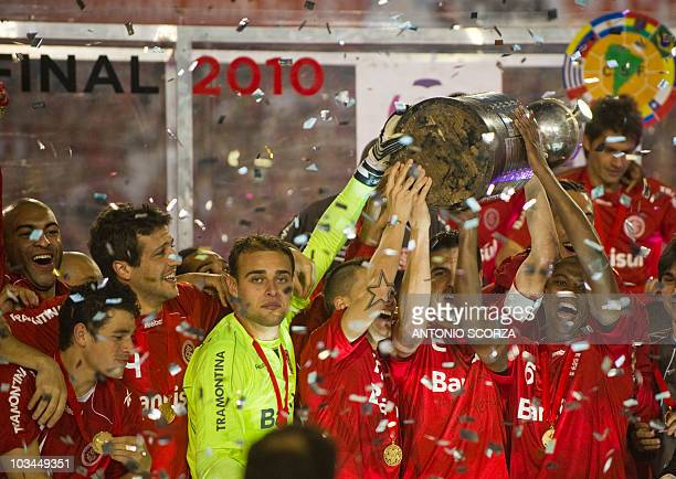 Brazil's Internacional team captain Bolivar holds the Libertadores Cup with teammates after defeat Mexico's Chivas 32 on August 18 2010 on their...