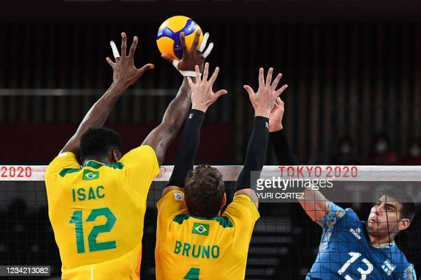 Brazil's Isac Santos and Bruno Rezende block a shot from Argentina's Ezequiel Palacios in the men's preliminary round pool B volleyball match between...