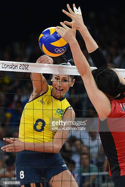 Brazil's Jaqueline Carvalho spikes as Japan's Erika Araki attempts to block during the Women's semifinal volleyball match between Brazil and Japan in...